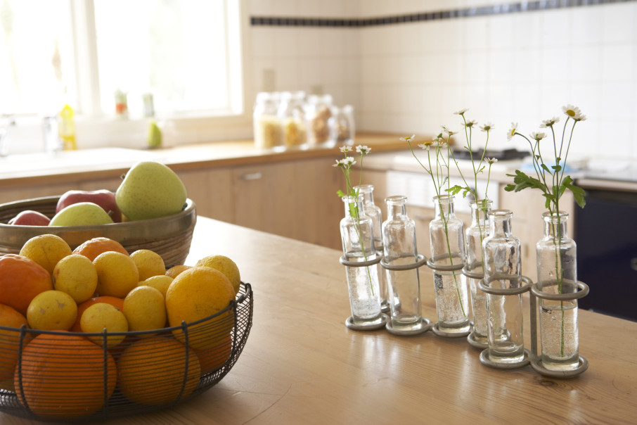 lemons and oranges in wire basket, apples in wooden bowl and flowers in glass bottle vases on wooden counter in kitchen