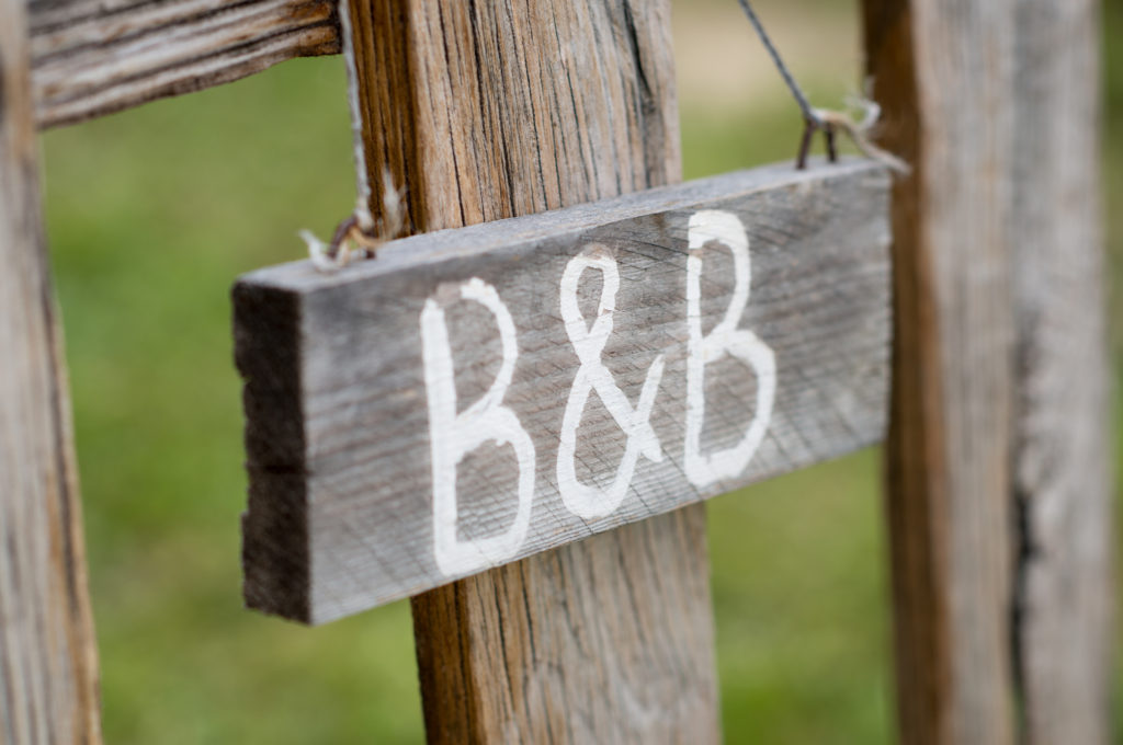Closeup Of Old Signboard Bed & Breakfast Hanging On Fence