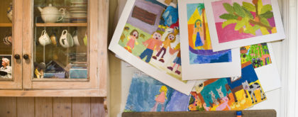 Children's paintings by cabinet