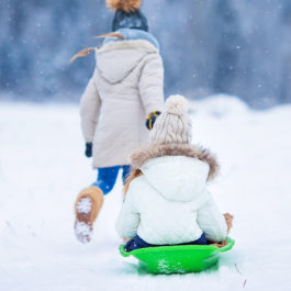 Adorable little happy girls sledding in winter snowy day. Family vacation on Christmas eve outdoors