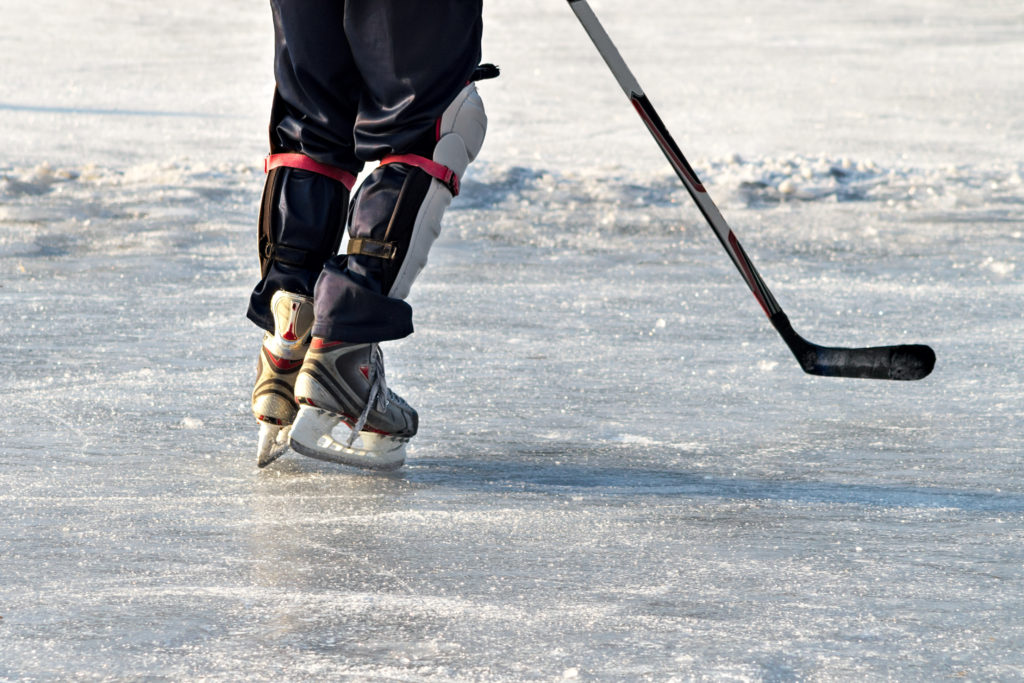 Close-up of skates on player feet during ice hockey. Hockey player practising on a frozen pond outdoor. People playing amateur hockey. Winter playing, fun, snow.