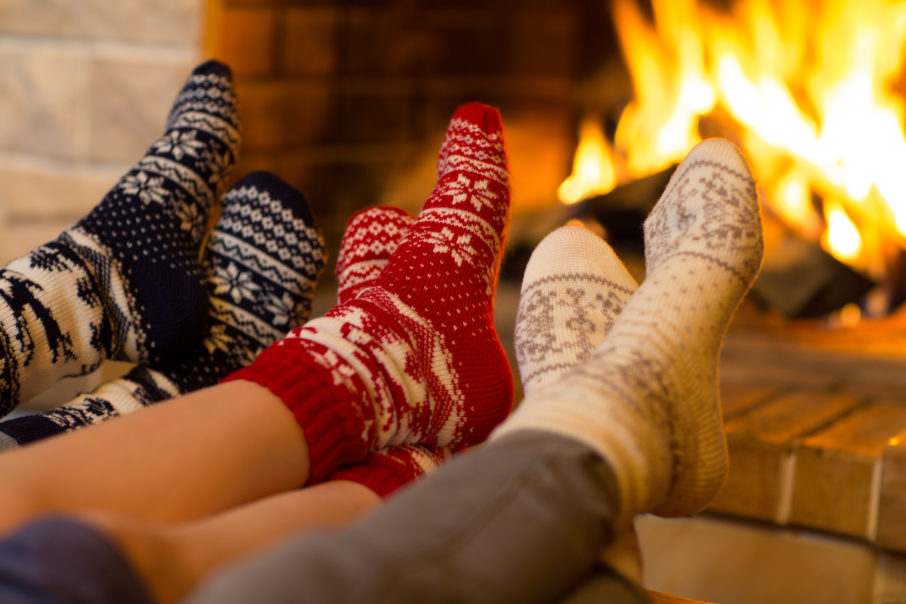 Family in socks near fireplace in winter or christmas