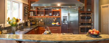 Breakfast bar in contemporary upscale home kitchen interior with granite countertops, accent lighting and stainless steel appliances including vent hood and refrigerator.