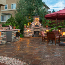 Paver patio with a fire pit, outdoor kitchen, pizza oven and lighting at dusk.