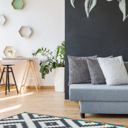 Stylish living room with sofa connected with bright workshop