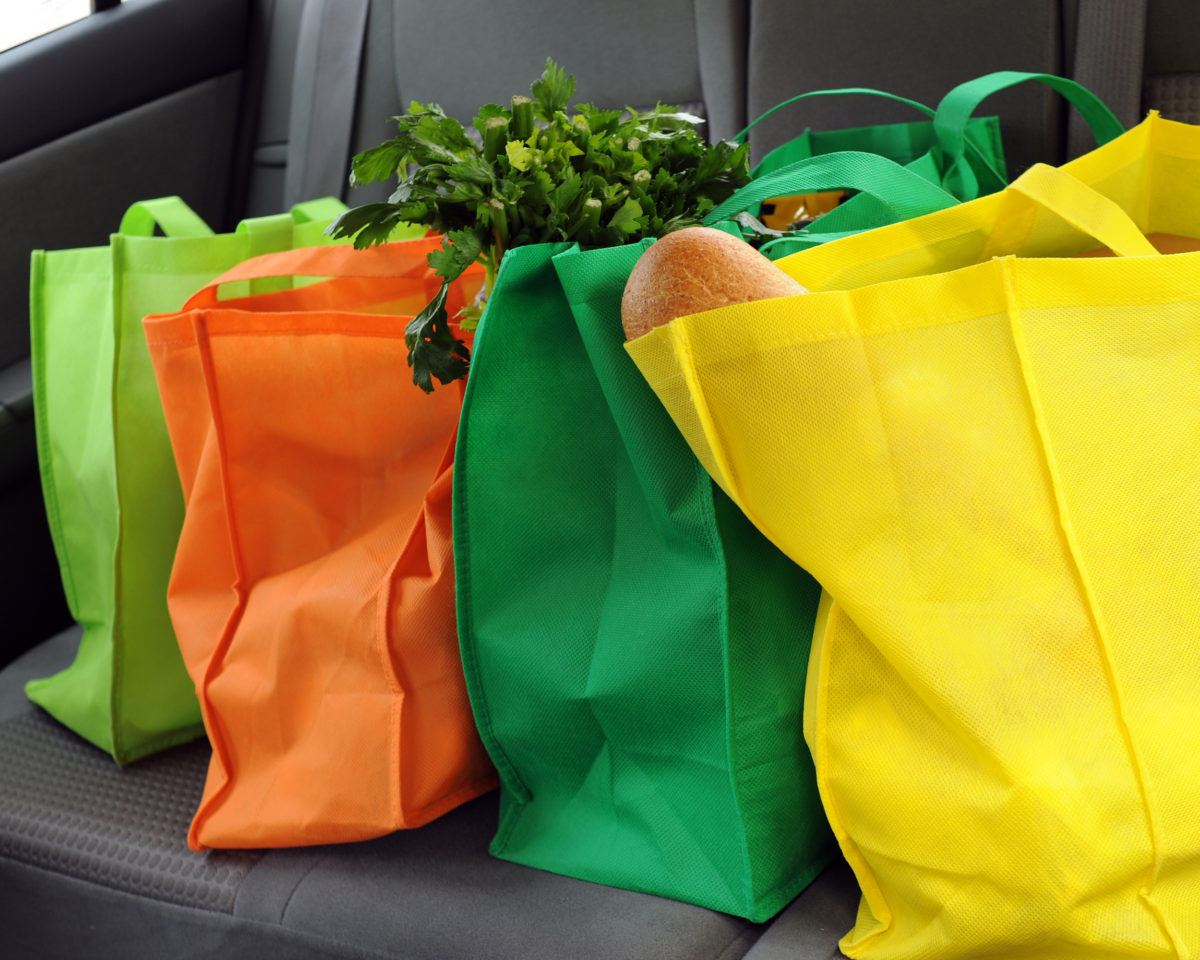 Four filled and colorful eco-friendly shopping bags in the back seat of a car.