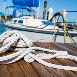 A sailboat tied up on a dock. Shot in Islamorada, Florida. Shallow depth of field with focus on rope and cleat.