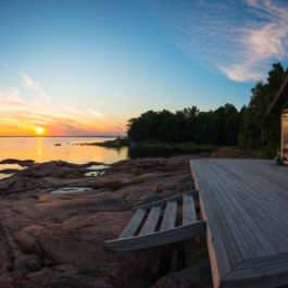 Summer cottage patio by the water at sunset
