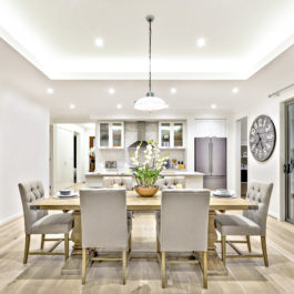 Modern dining room with hanging lamps on, there are chairs and table setup with fancy items on the wooden floor