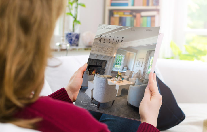 Blond woman holding a blank brochure or book cover with copy space. The photo was taken indoors in a domestic room by photographing over the woman's shoulder.
