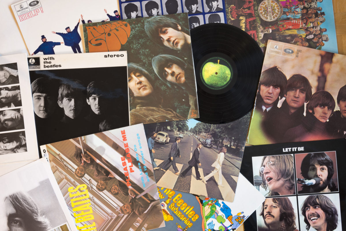 Gothenburg, Sweden - March 2, 2014: The Beatles musical pop/rock band from England. Vinyl record covers and one black vinyl record with a green apple on the label. Originals from the sixties, old and well used