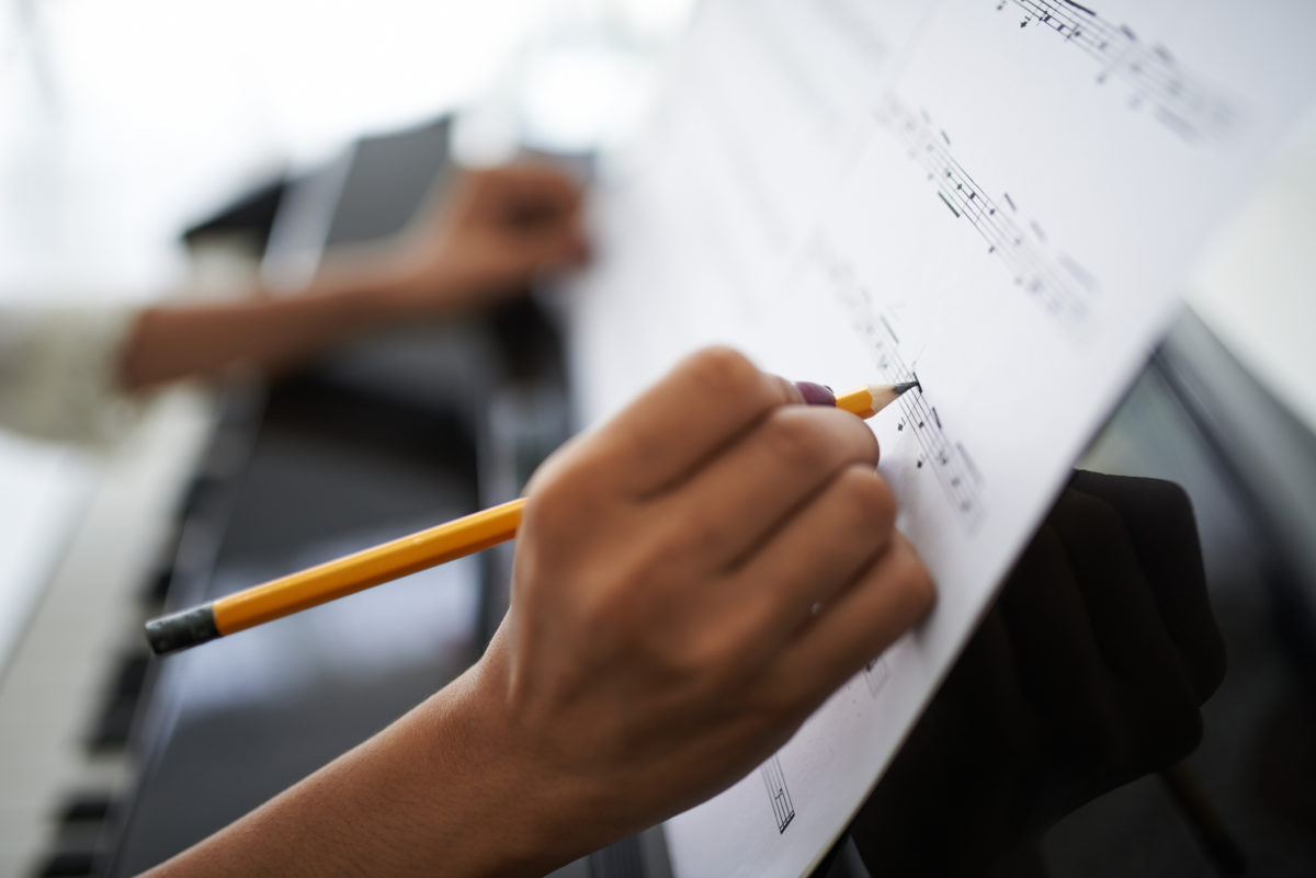 Close-up of female hands correcting music score