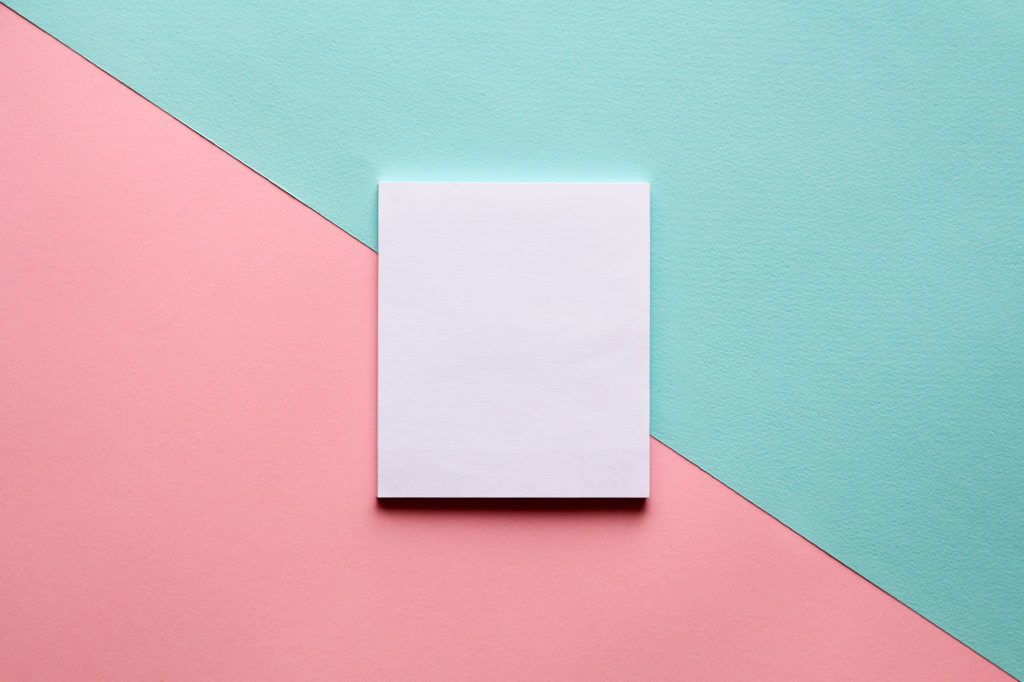 Abstract geometric diagonal watercolor paper background in soft pastel pink and blue trend colors with white notebook on it.