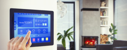 Person using home automation to control lighting, heating, air conditioning ... etc in modern apartment with fireplace, large windows with blinds, wooden floor and concrete ceiling.