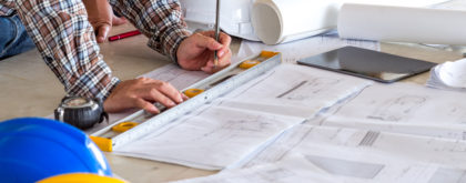 Engineer/architect/worker man discussing about building plan for construction at job site, working on desk/table with drawing/blueprint/business plan