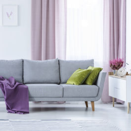 Elegant living room with big comfortable grey couch with olive green pillows and violet blanket in the middle of stylish living room with heater in pots and lilac curtains