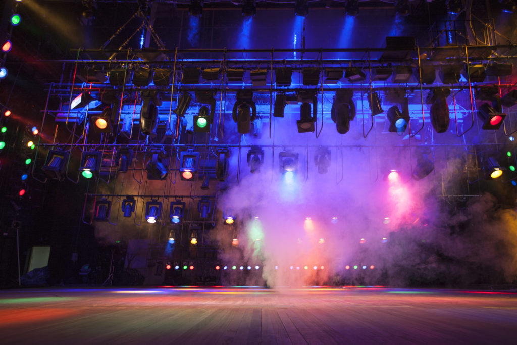 Light effects on stage created with theatrical lighting equipment and a smoke machine